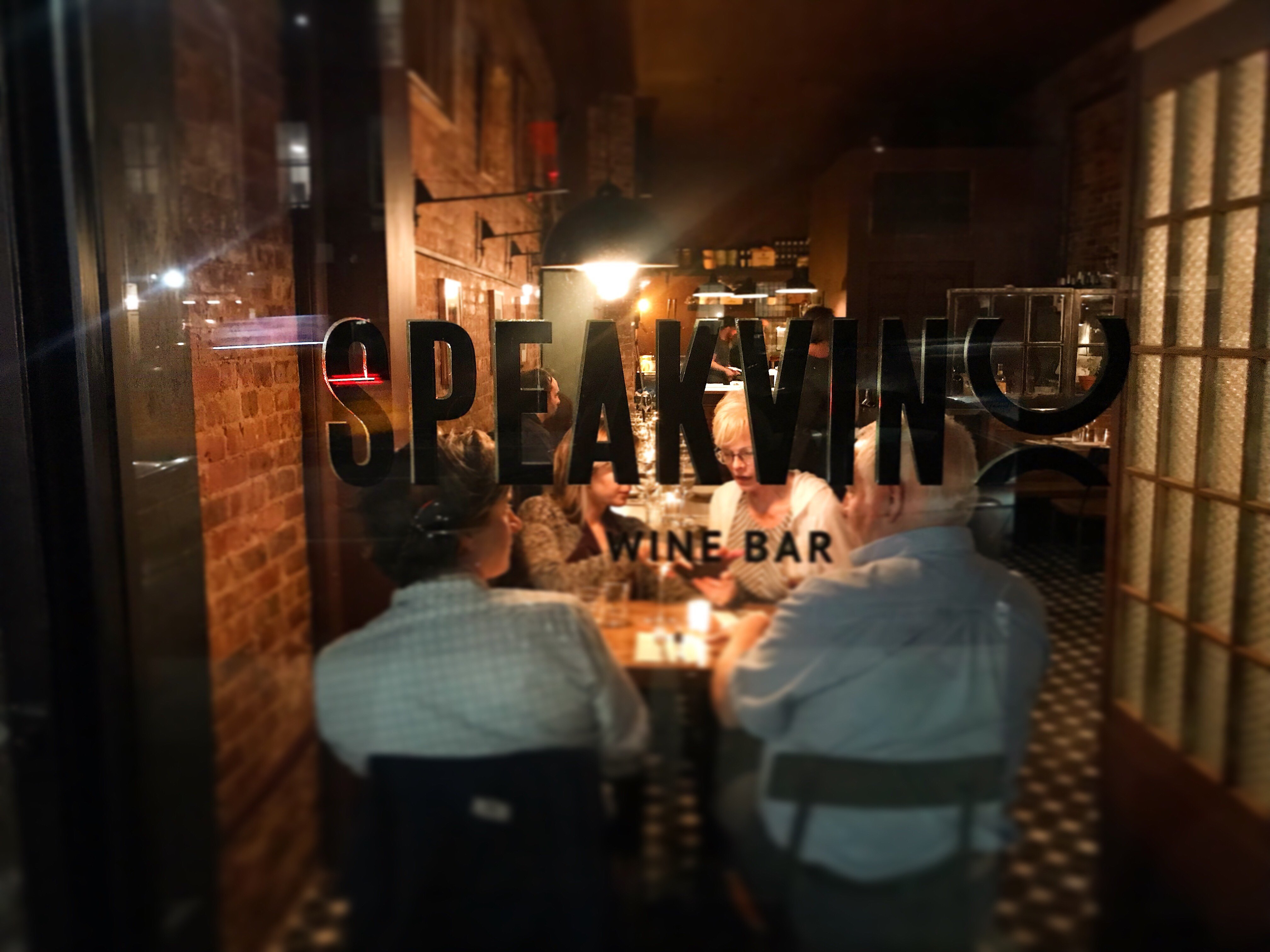 Customers dining at Speakvino, seen through the front window that displays the bar's name