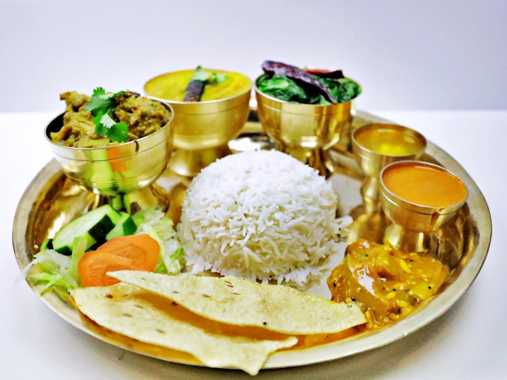 A gold-colored plate of Nepali food surrounded by small gold cups, also filled with food.