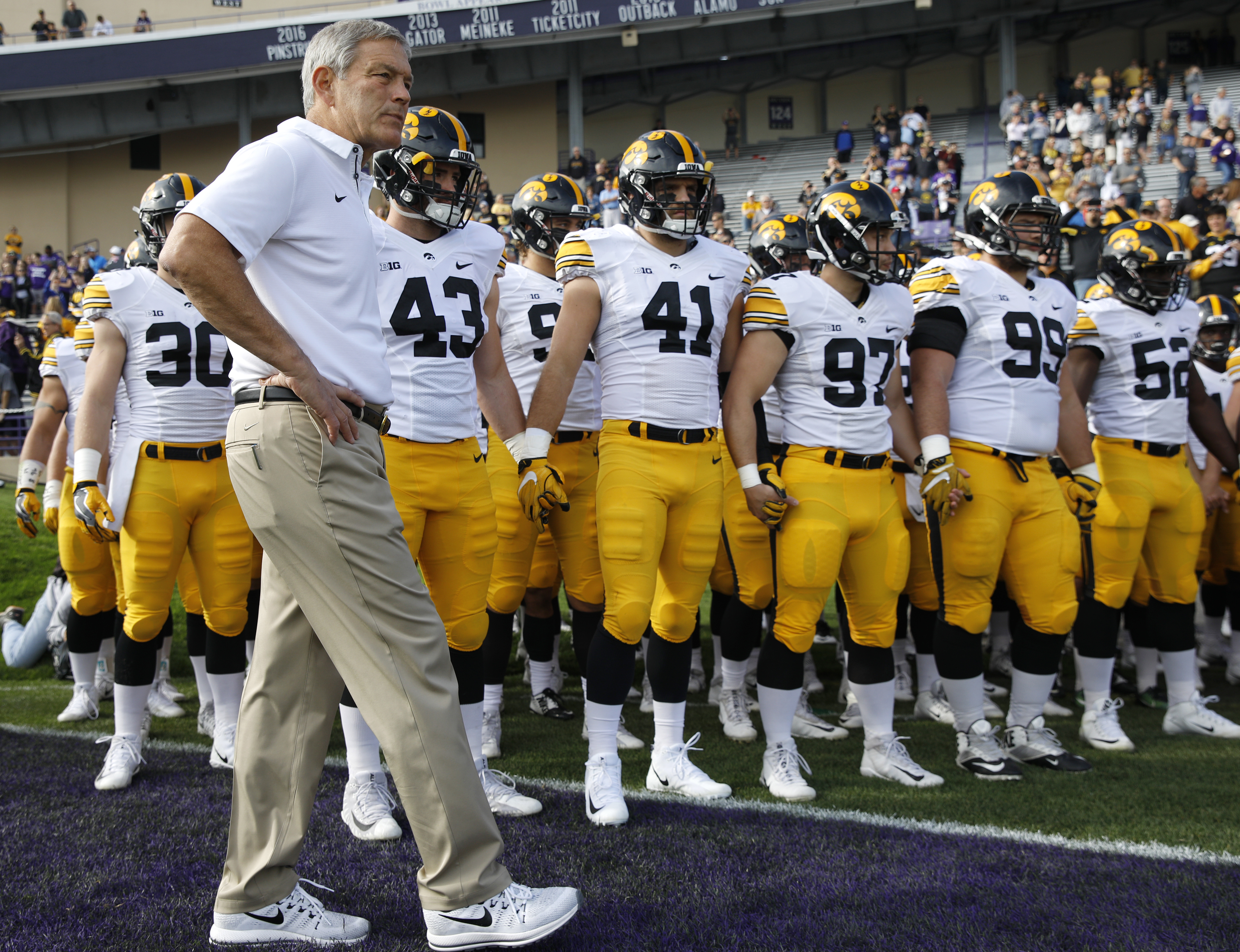 Iowa coach Kirk Ferentz waits with his team.