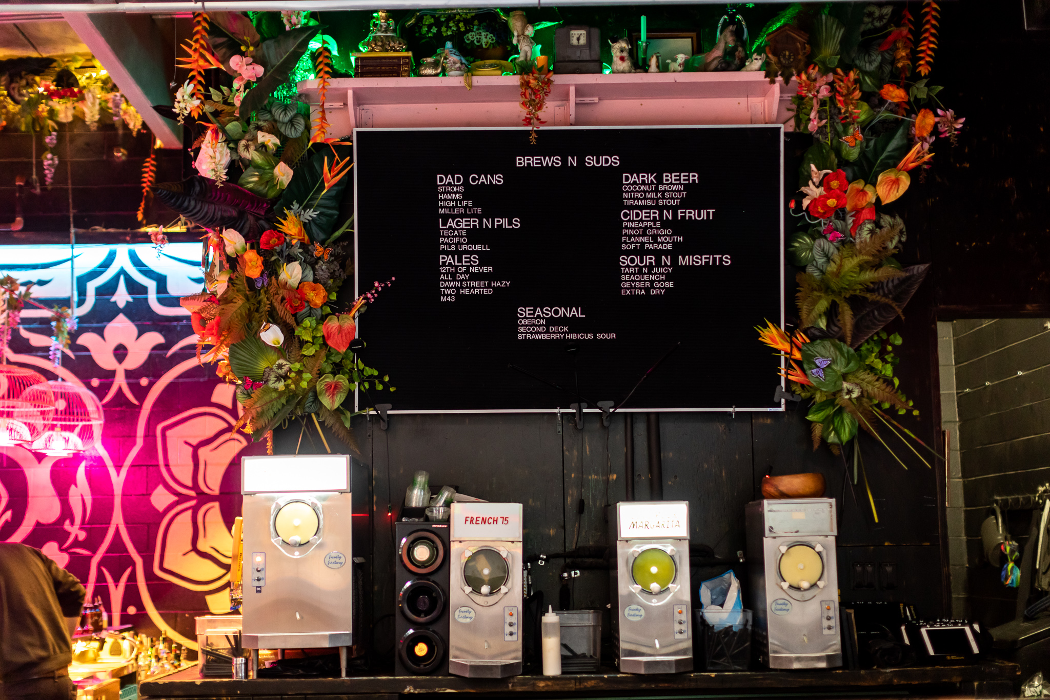 A menu board surrounded by colorful flowers is hung above frozen cocktail machines.