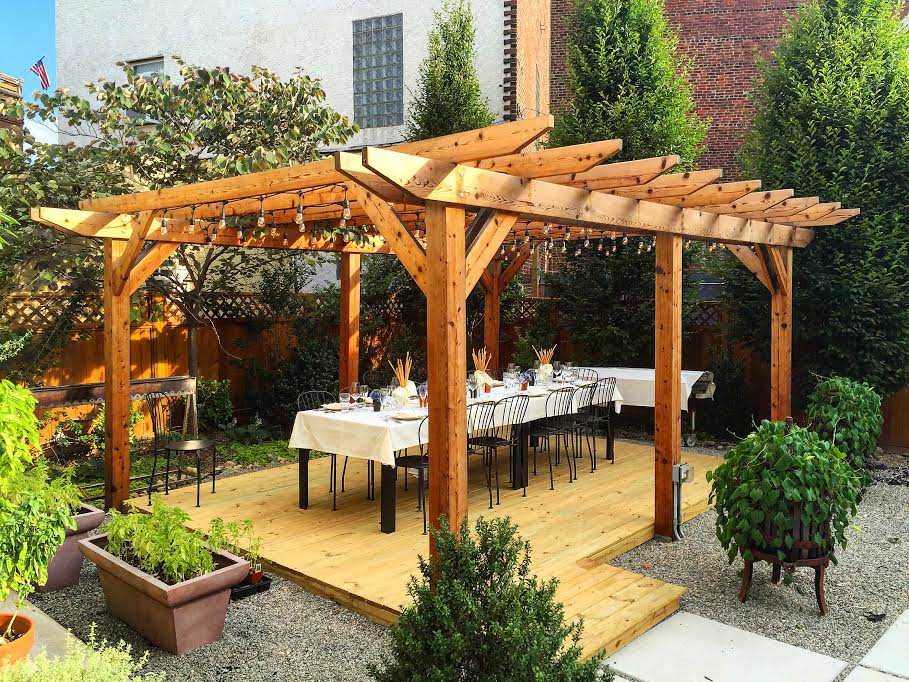 table set up under pergola surrounded by greenery