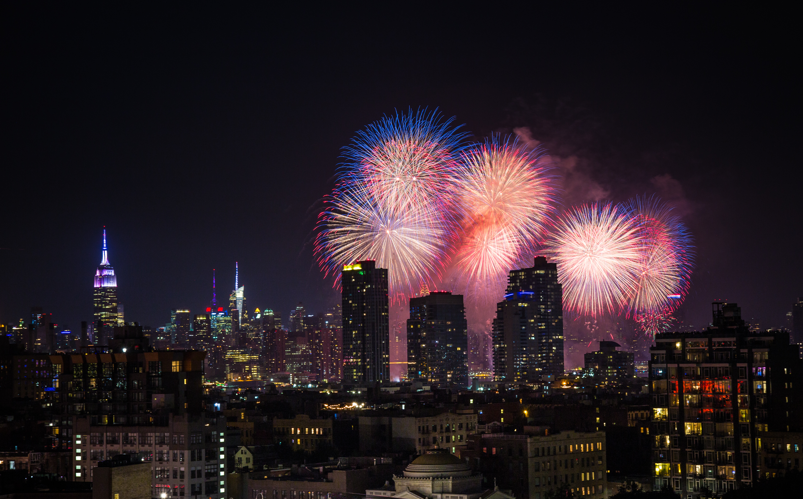 Colorful fireworks over the New York City skyline at night.