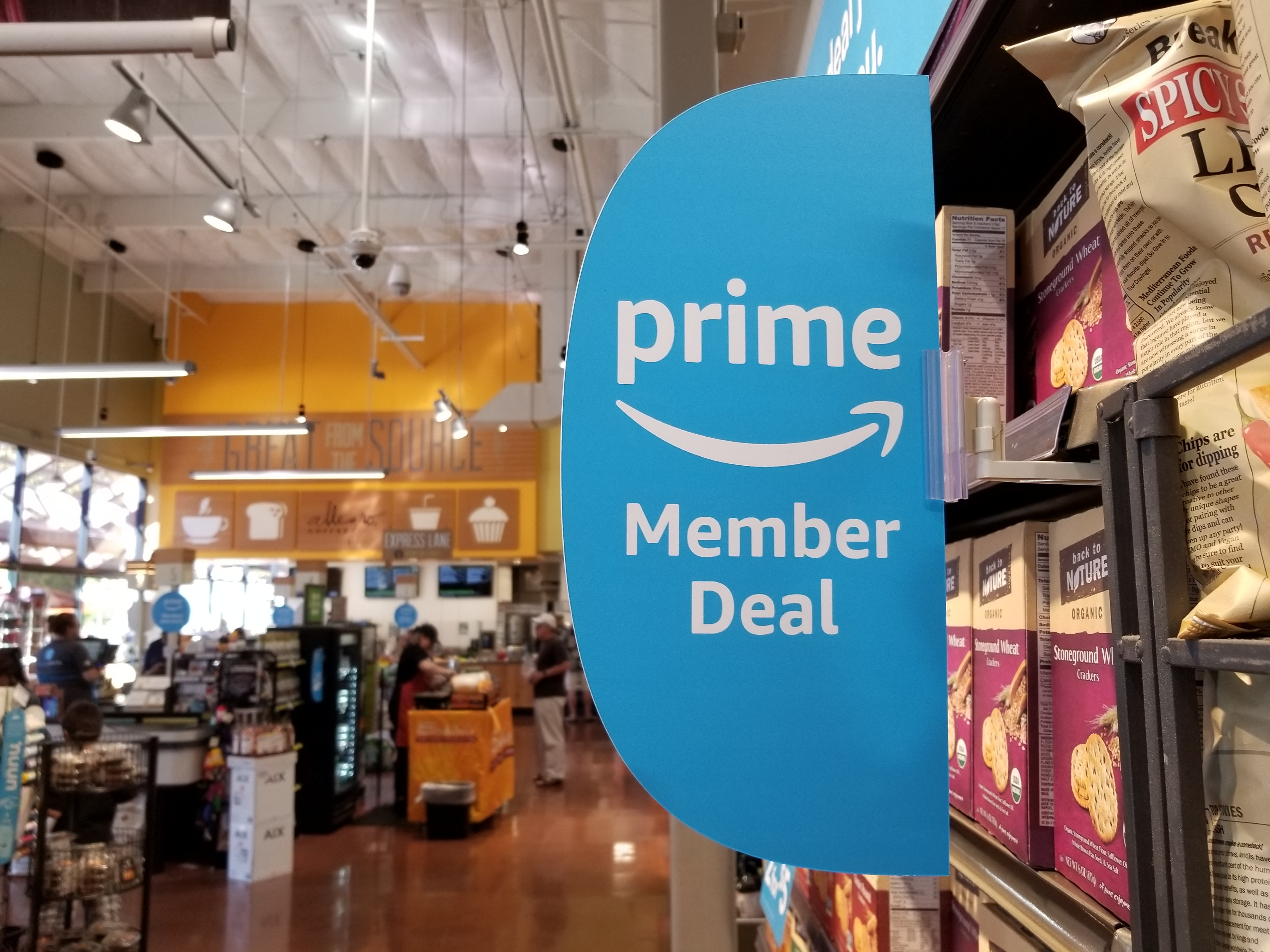Signage at a Whole Foods Market grocery store, on a shelf of chips, advertising new discounts for members of the Amazon Prime service from Amazon.