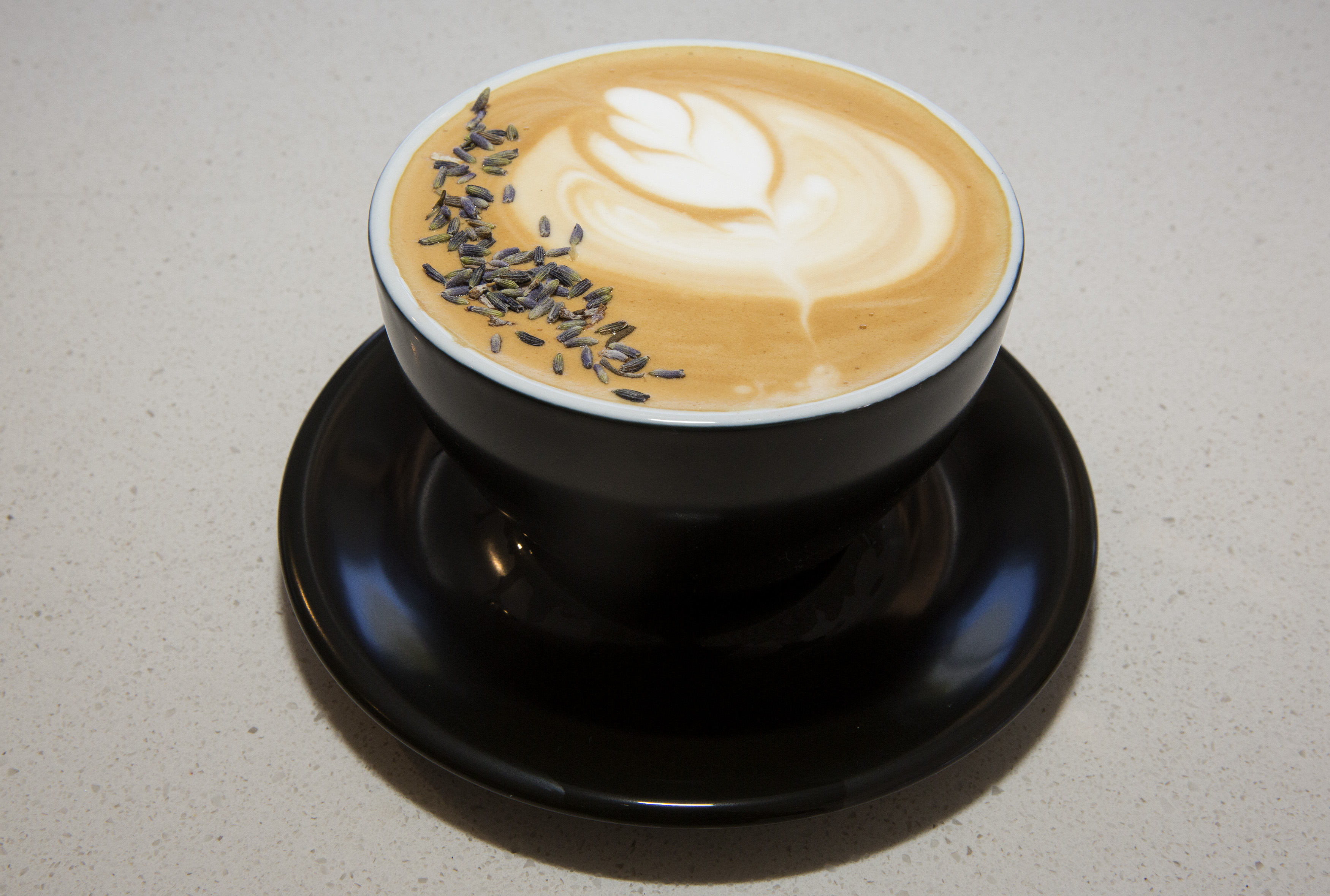 A hot coffee latte with dried lavender sprinkled on the head.