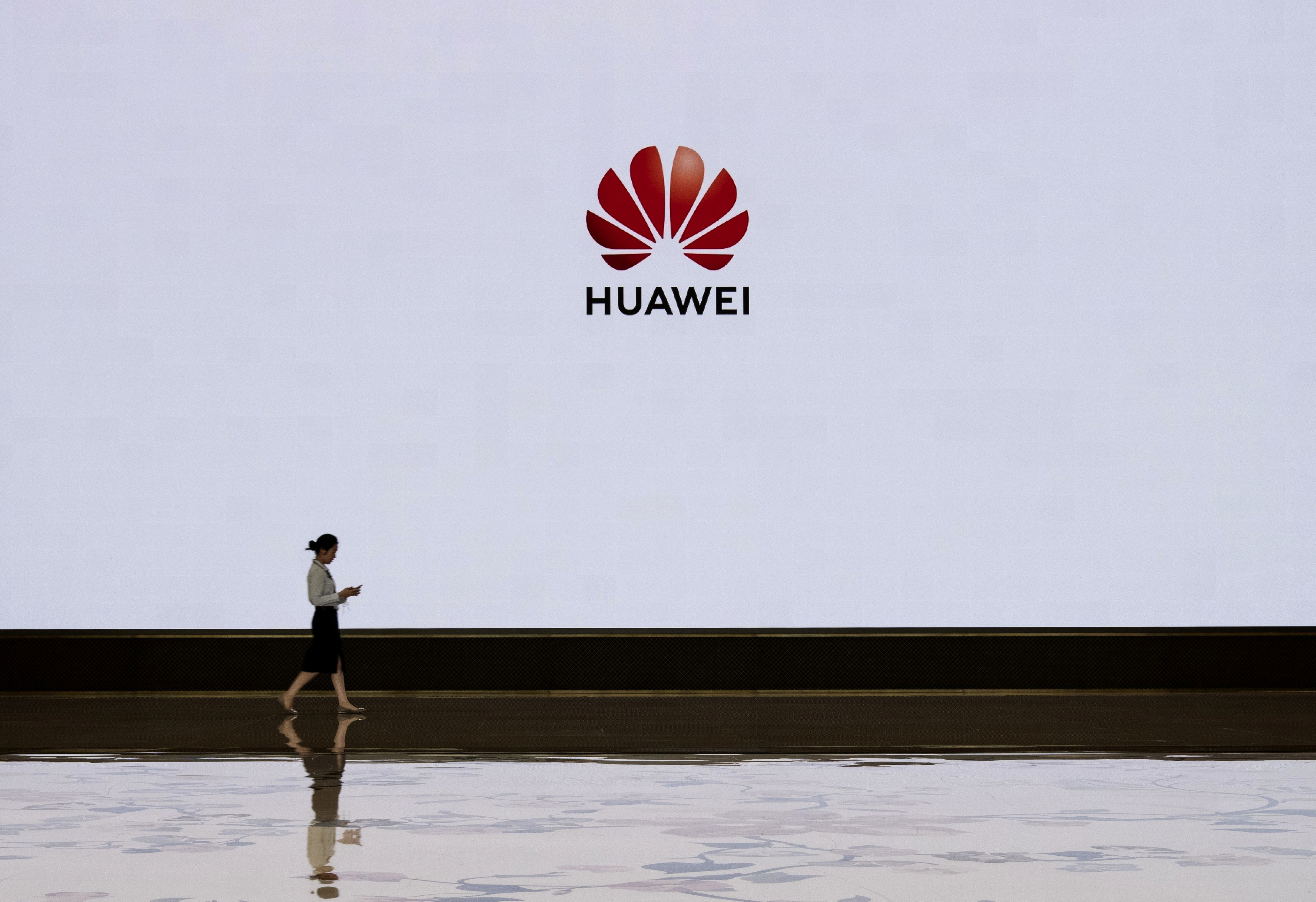 """A person walking past a sign reading """"Huawei."""""""