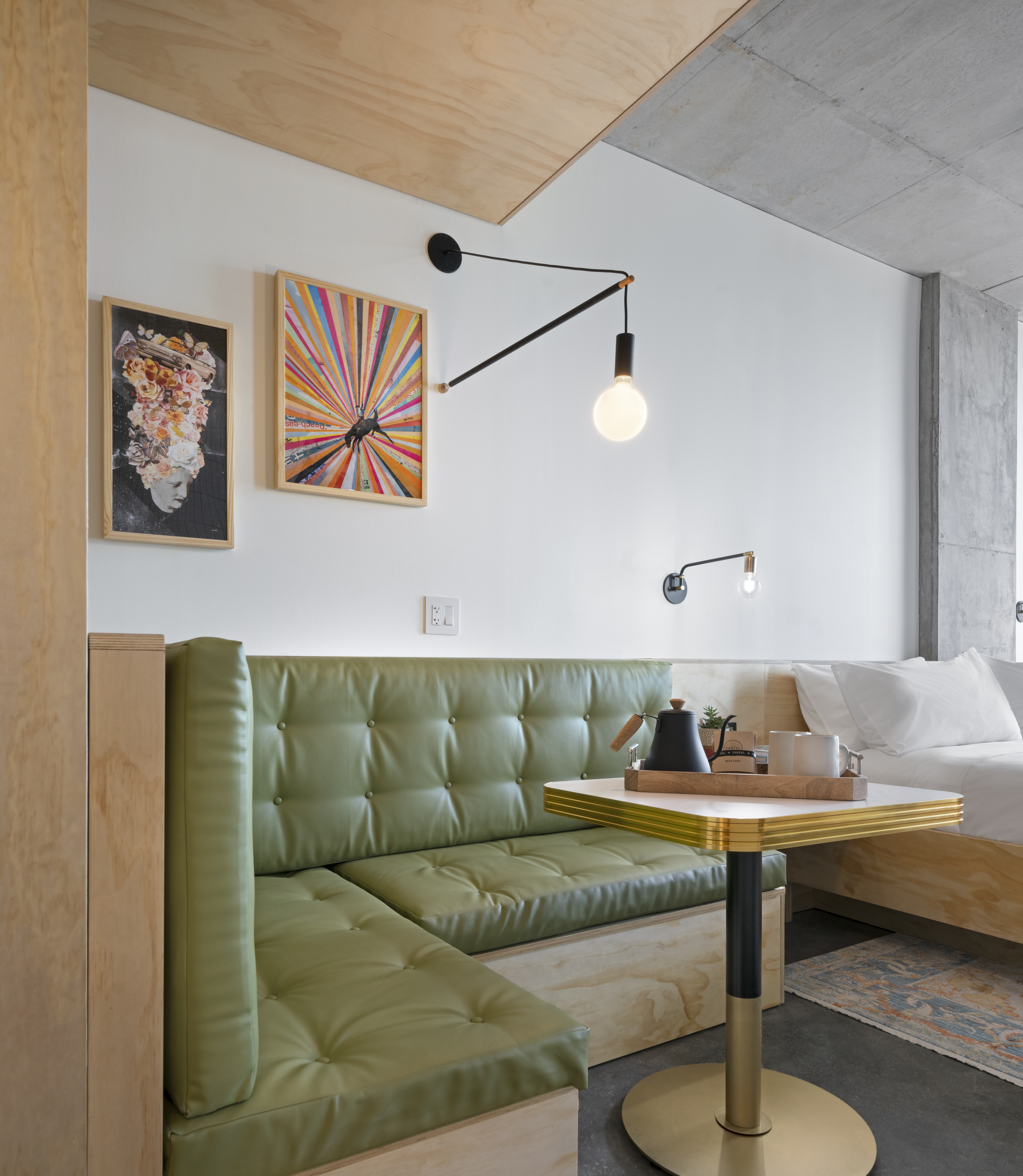 hotel room with small avocado green banquette, bed, art, mod light fixture