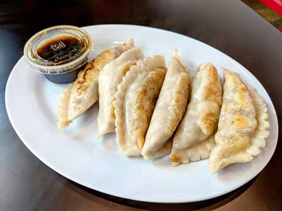 Six pan-seared dumplings sit on a white plate. A plastic cup of a soy-based dipping sauce is next to them.