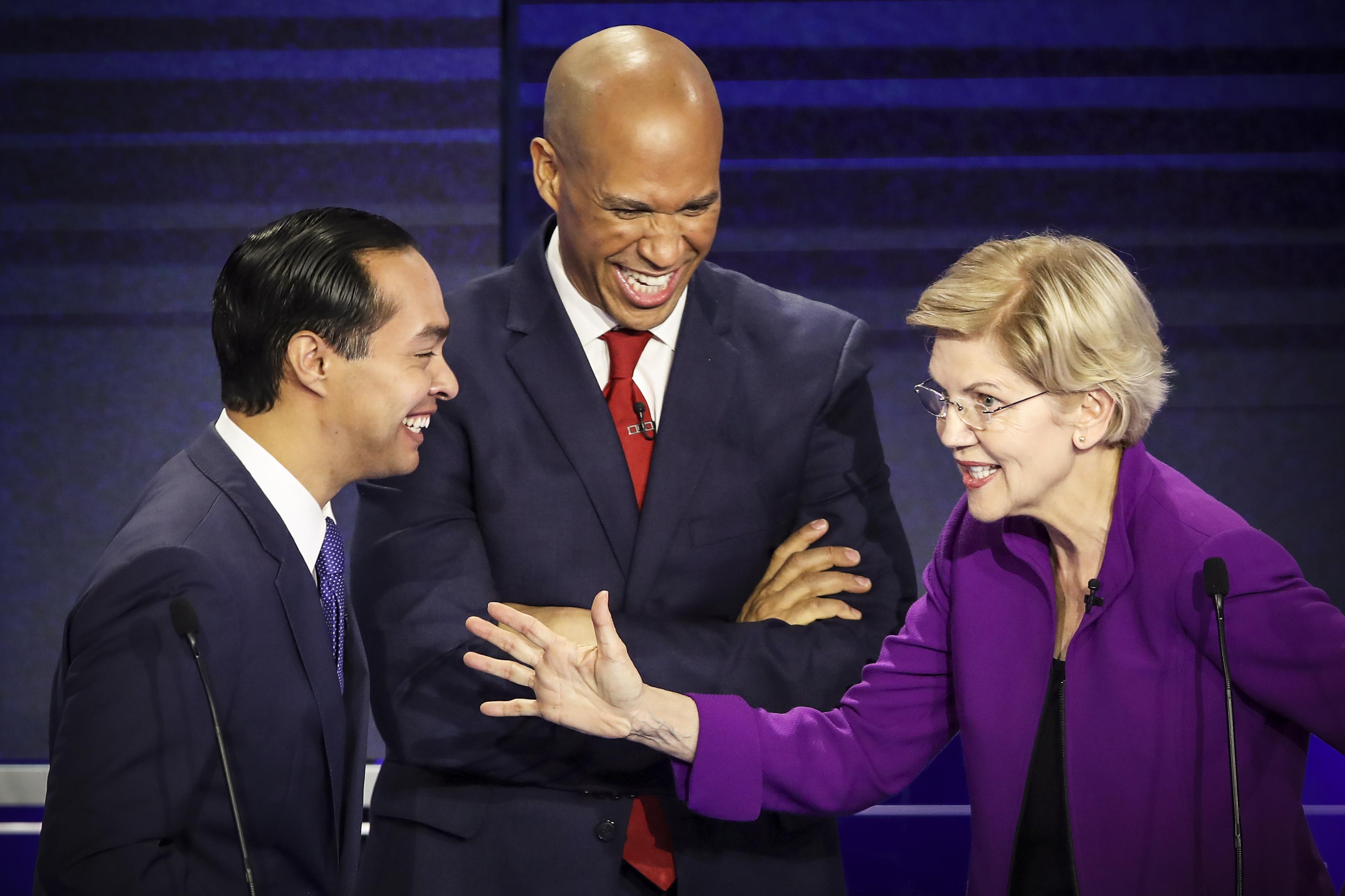 Former housing secretary Julian Castro, Sen. Cory Booker (D-NJ) and Sen. Elizabeth Warren (D-MA) interact during the first night of the Democratic presidential debate on June 26, 2019 in Miami, Florida.