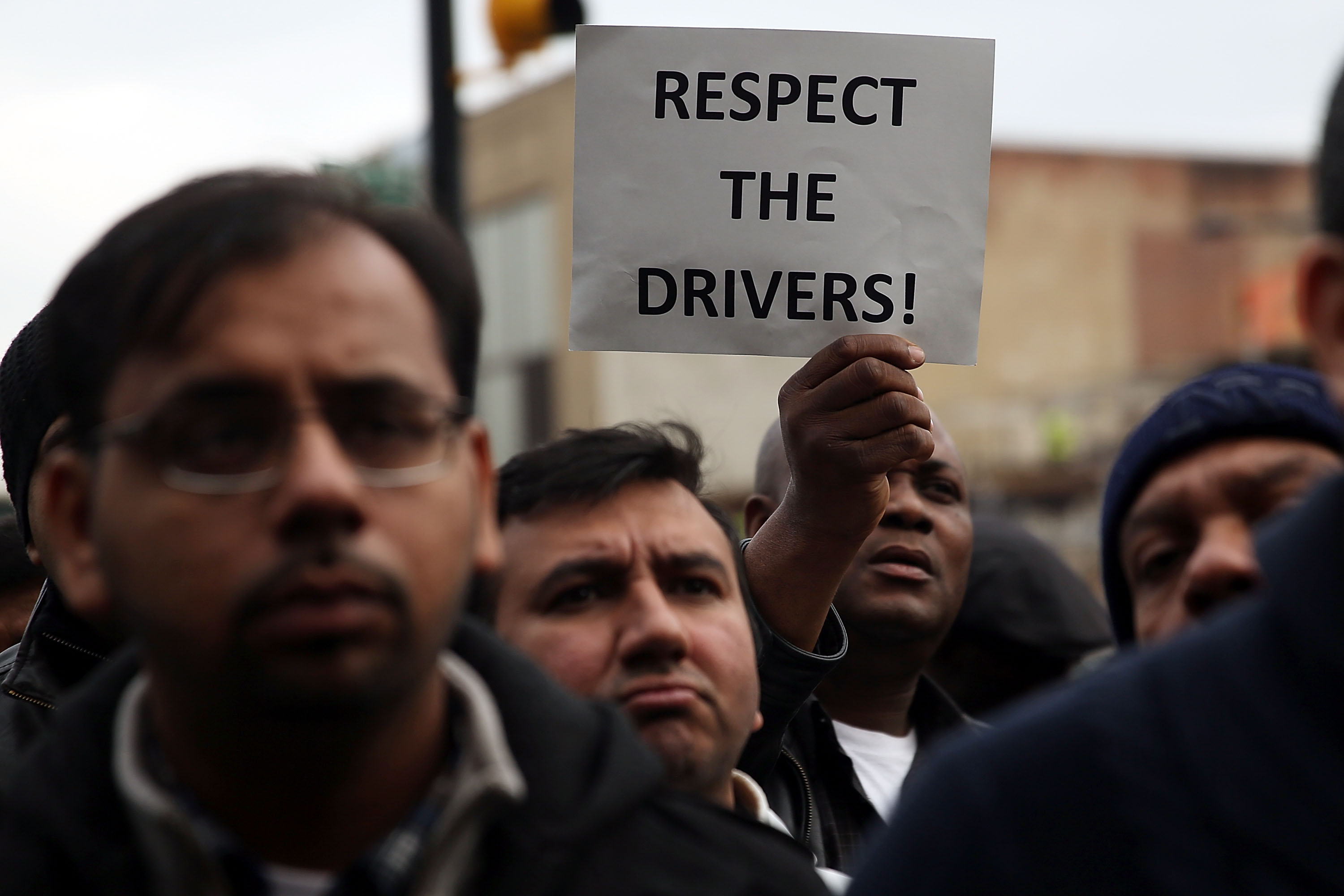 "Drivers for Lyft and Uber protest. One holds a sign reading ""Respect the drivers!"""