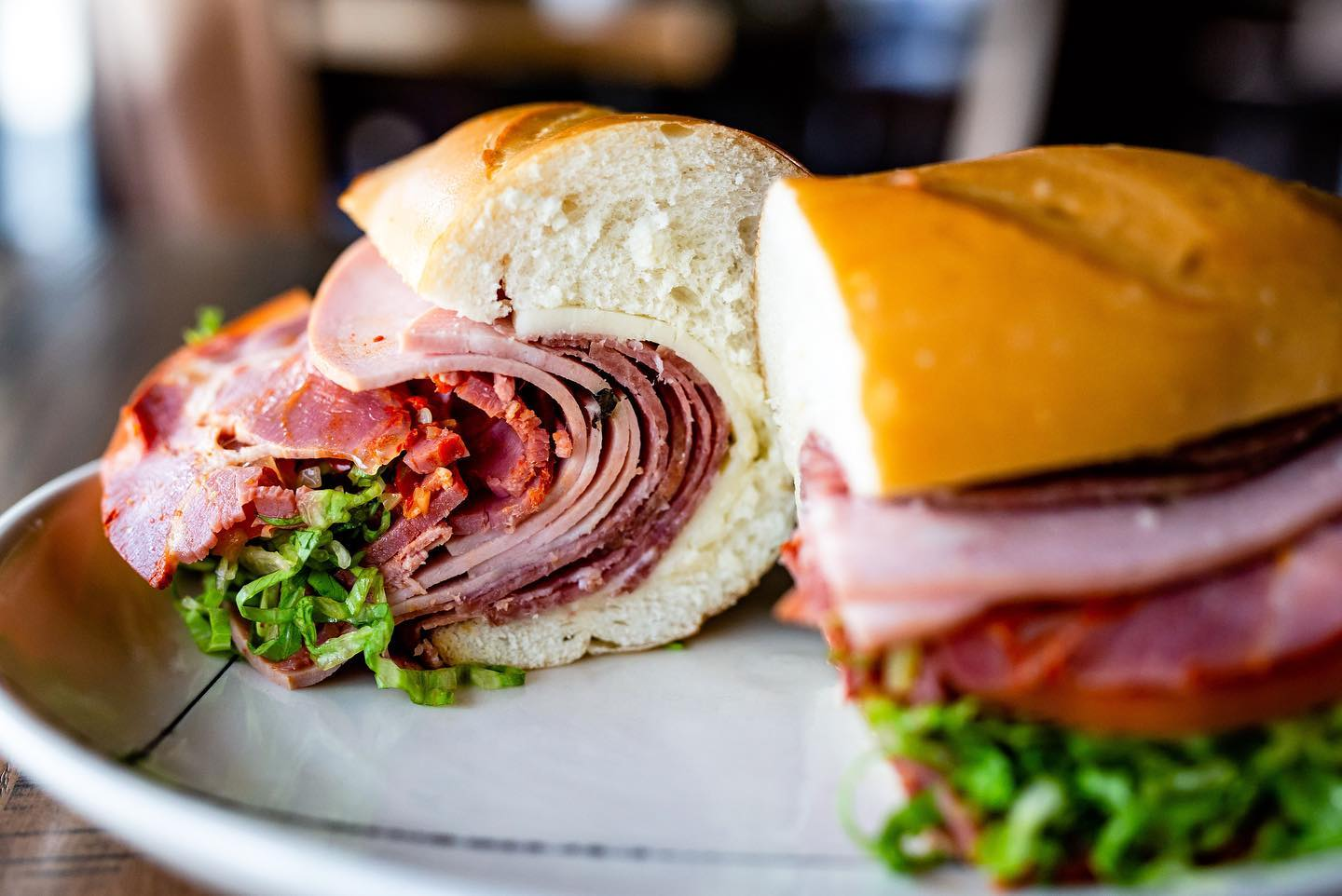 a close up of an Italian sandwich with folds of mortadella, salami, provolone, lettuce, tomato, onion, pepper relish and mayo on a hoagie.