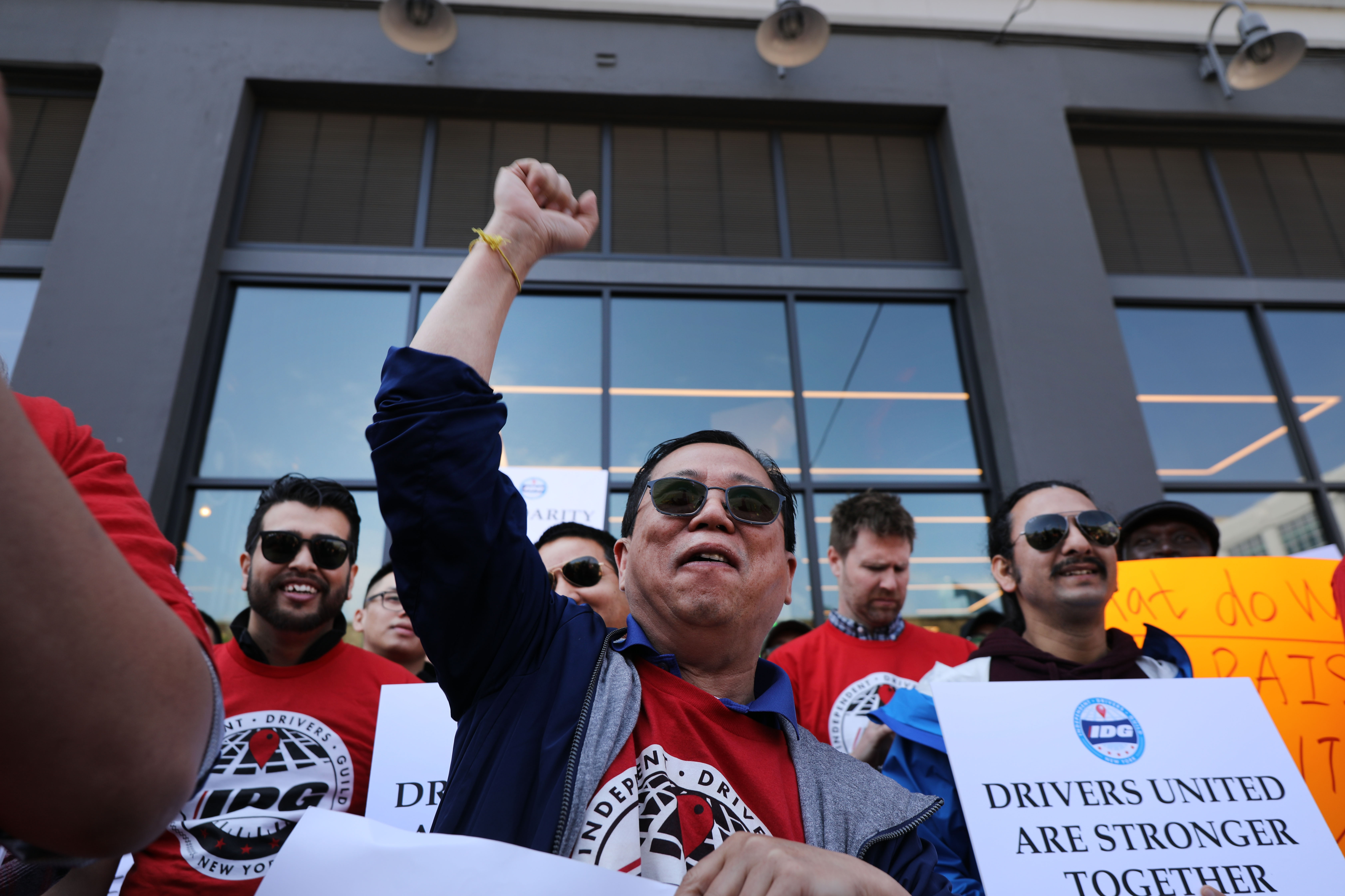 """A ride-share driver at a rally raises his fist while another holds a sign that reads, """"Drivers united are stronger."""""""