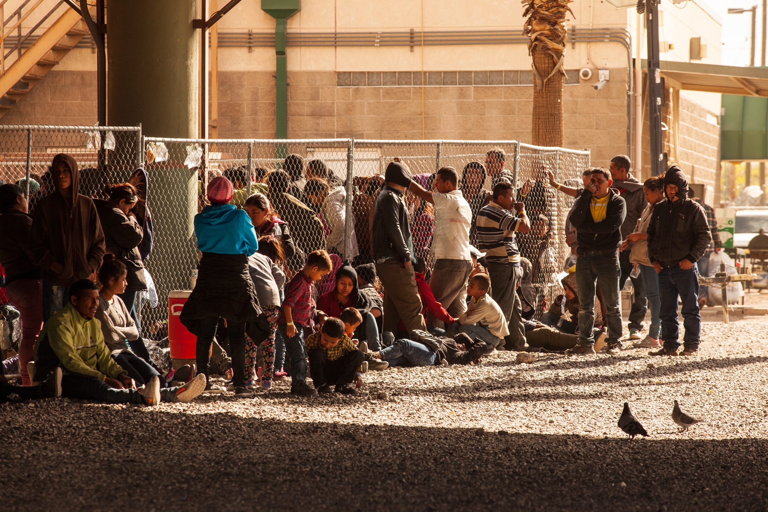 a large group of migrants gathered behind a fence underneath an overpass