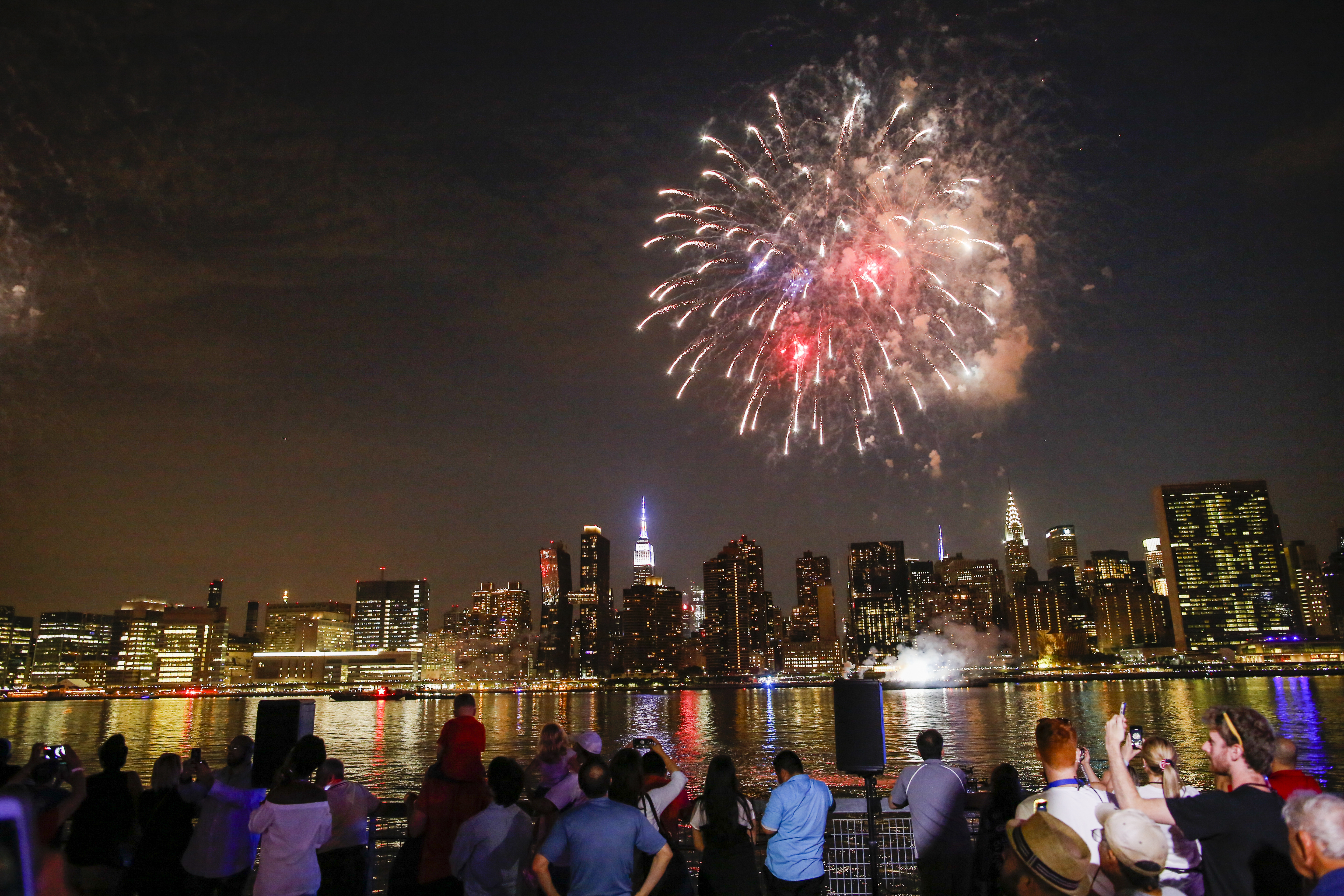 People stand at a waterfront watching a bright colorful fireworks display over the night skyline of New York City.