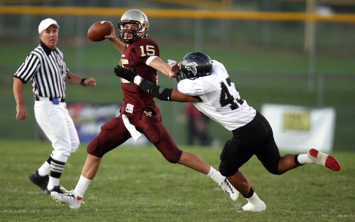 Lone Peak quarterback Chase Hansen throws a pass as Alta's Tupou Aagard tackles him during the first half of a football game at Lone Peak High School in Highland on Friday, September 24, 2010.