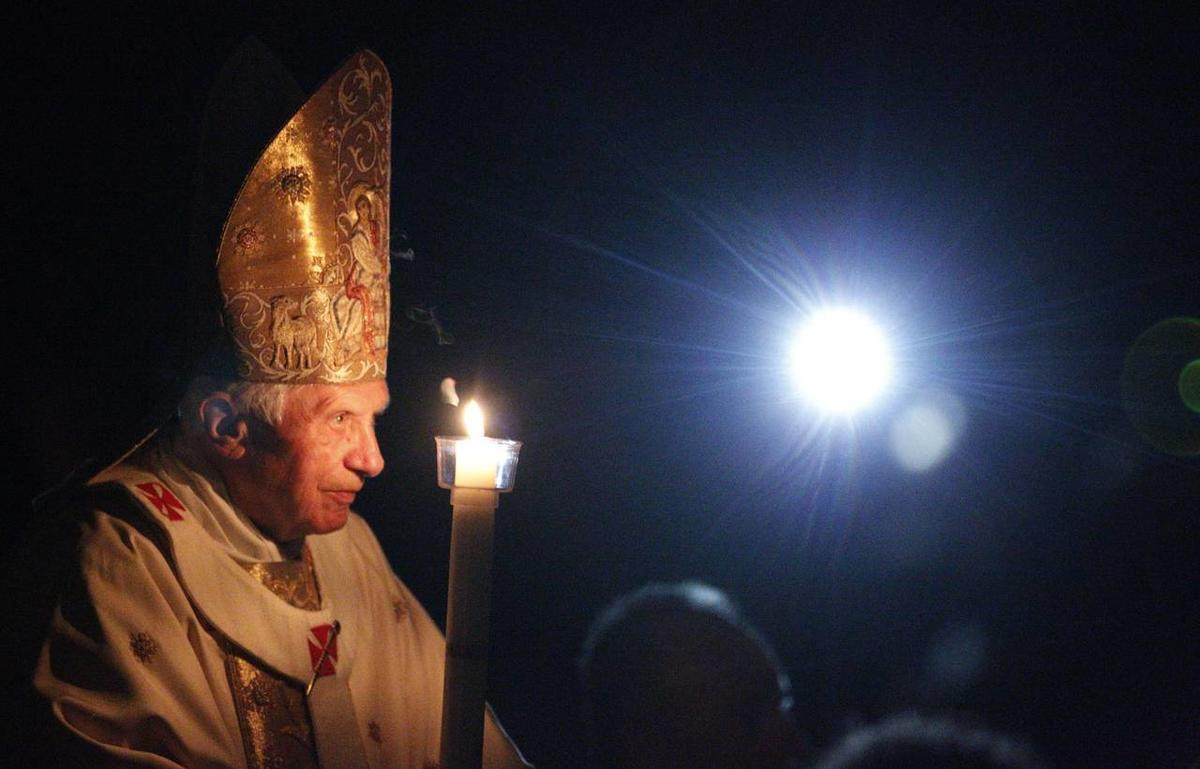 Pope Benedict XVI, holding a tall, lit, white candle, enters a hushed and darkened St. Peter's Basilica, at the Vatican Saturday, April 7, 2012, to begin the Vatican's Easter vigil service.