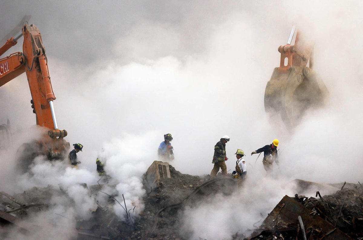 FILE - In this Oct. 11, 2001 file photo, firefighters make their way over the ruins and through clouds of smoke at the World Trade Center in New York.  Three retired firefighters who worked at ground zero have died on the same day from 9/11-related illnes