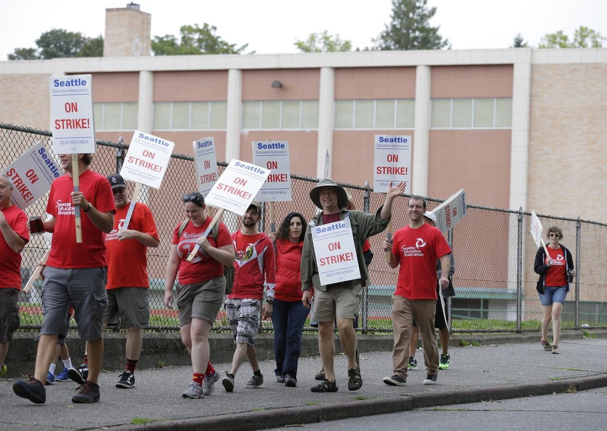 Striking Seattle School District teachers and other educators  walk a picket line, Thursday, Sept. 10, 2015, near Franklin High School in Seattle. (AP Photo/Ted S. Warren)