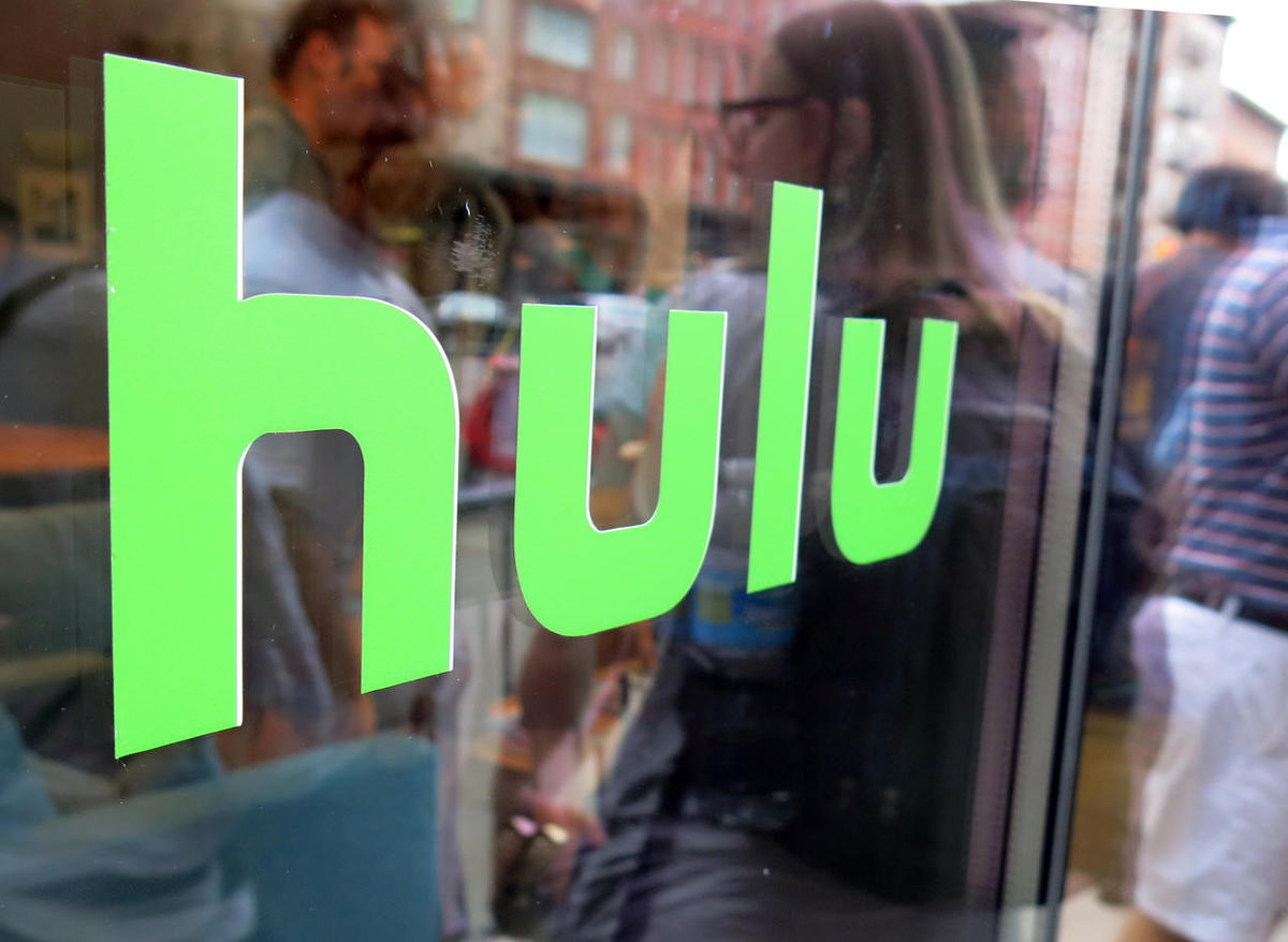 FILE - This June 27, 2015, file photo, shows the Hulu logo on a window at the Milk Studios space in New York. Hulu said Monday, Aug. 8, 2016, that the company is dropping the free TV episodes that it was initially known for as it works on launching a skin