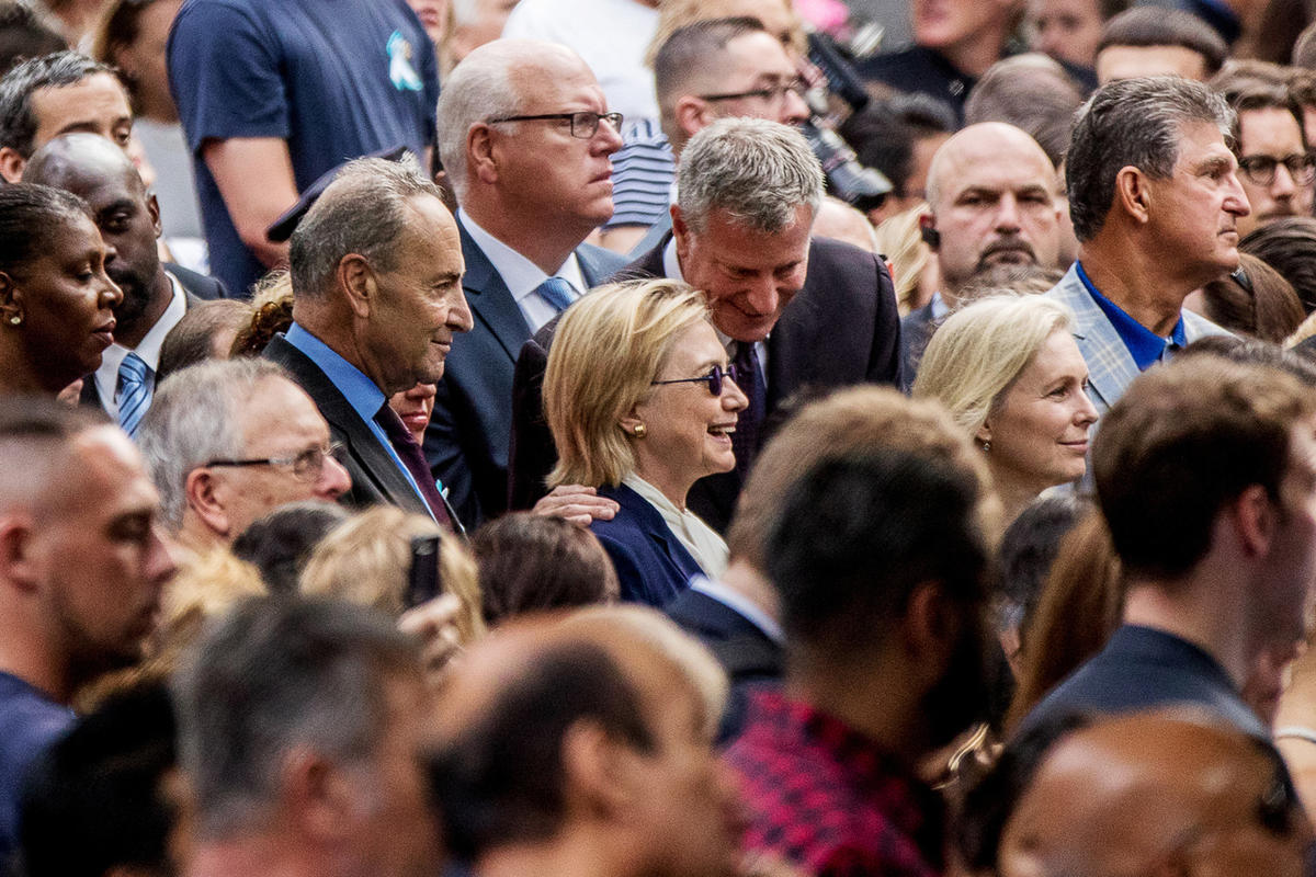 Democratic presidential candidate Hillary Clinton, center, accompanied by Sen. Chuck Schumer, D-N.Y., left, and Rep. Joseph Crowley, D-N.Y., second from left, speaks with New York Mayor Bill de Blasio, center right, during a ceremony at the Sept. 11 memor