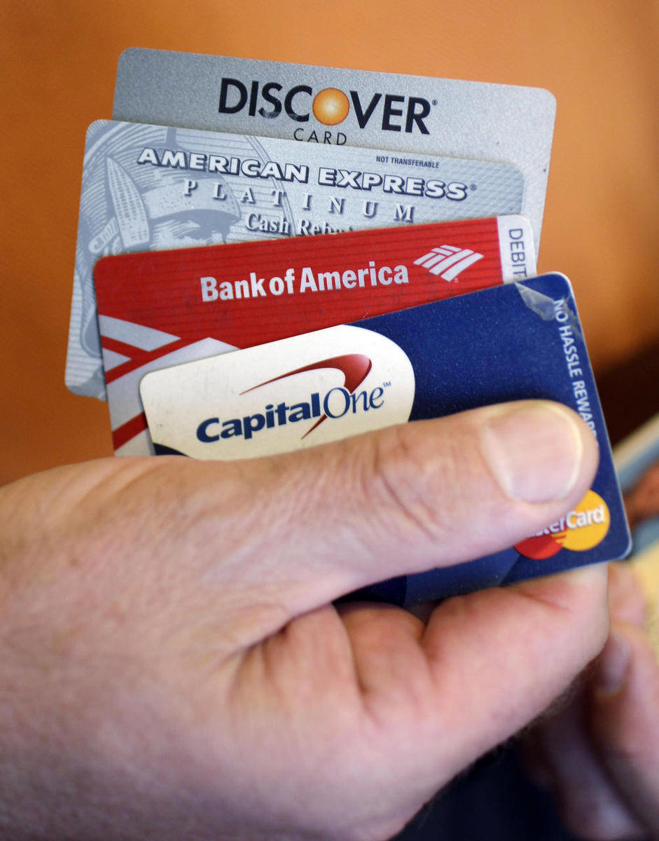 Steve Wheelock holds up his Discover Card along with his American Express, Bank of America and Capital One Visa credit cards in San Francisco, Wednesday, June 22, 2011. Discover Financial Services said Thursday, June 23, its second-quarter profit more tha