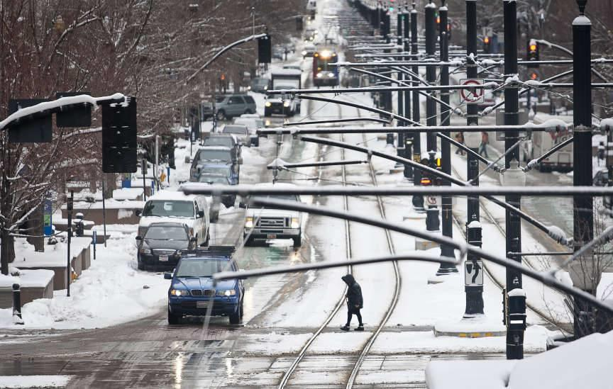 A pedestrian walks along the crosswalk at the intersection of 200 S. and Main Street in Downtown Salt Lake City as snow falls, Friday, Dec. 28, 2012.