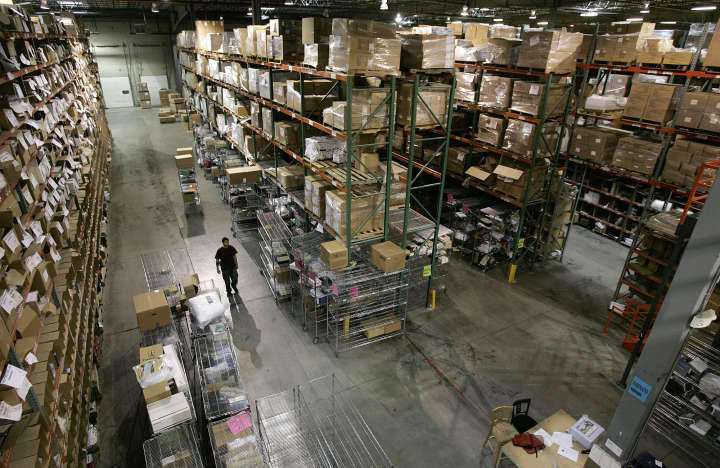 A worker walks between the rows and rows of merchandise in stock at Overstock.com's warehouse and distribution center Friday, March 31, 2006, in Salt Lake City.