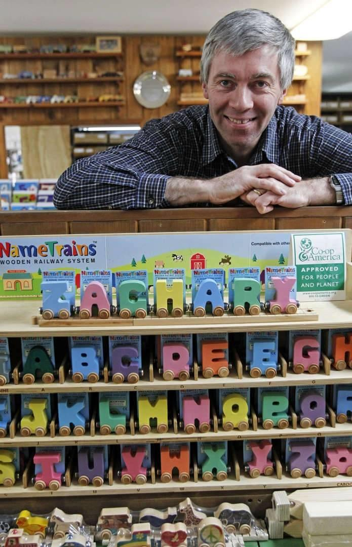 In this Friday, Feb. 22, 2013, photo, Mike Rainville poses with some of his products at the Maple Landmark Woodcraft factory in Middlebury, Vt. Rainville works with multiple generations of his family at the factory. Experts say family businesses are more