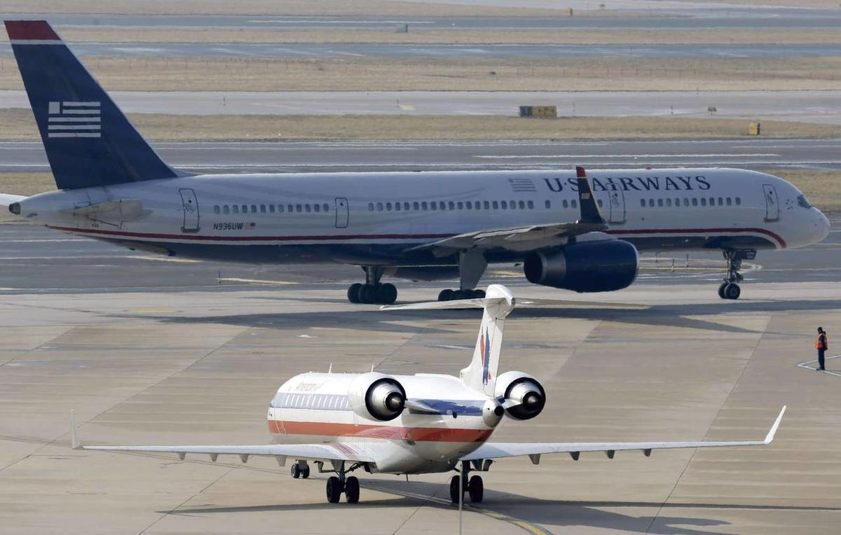 An American Airlines jet taxis near a US Airways plane at the Philadelphia International Airport in February.