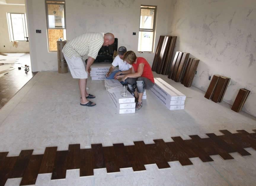 Kevin and Steffani Raff take a moment to sign mortgage papers with their broker, Rick Lyman, as they are laying their own wood floor to help them save money while building their new home this past summer in Saratoga Springs, Utah. Forty percent of those o