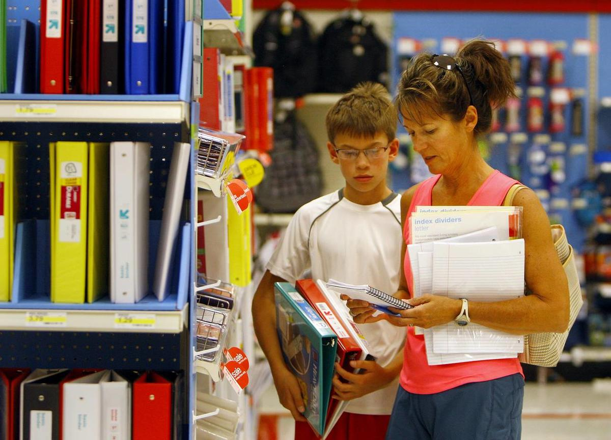 Lynette Boatright looks over her list of required supplies as her son Carter, 11, looks on at Target on Friday afternoon in Casper, Wyo.