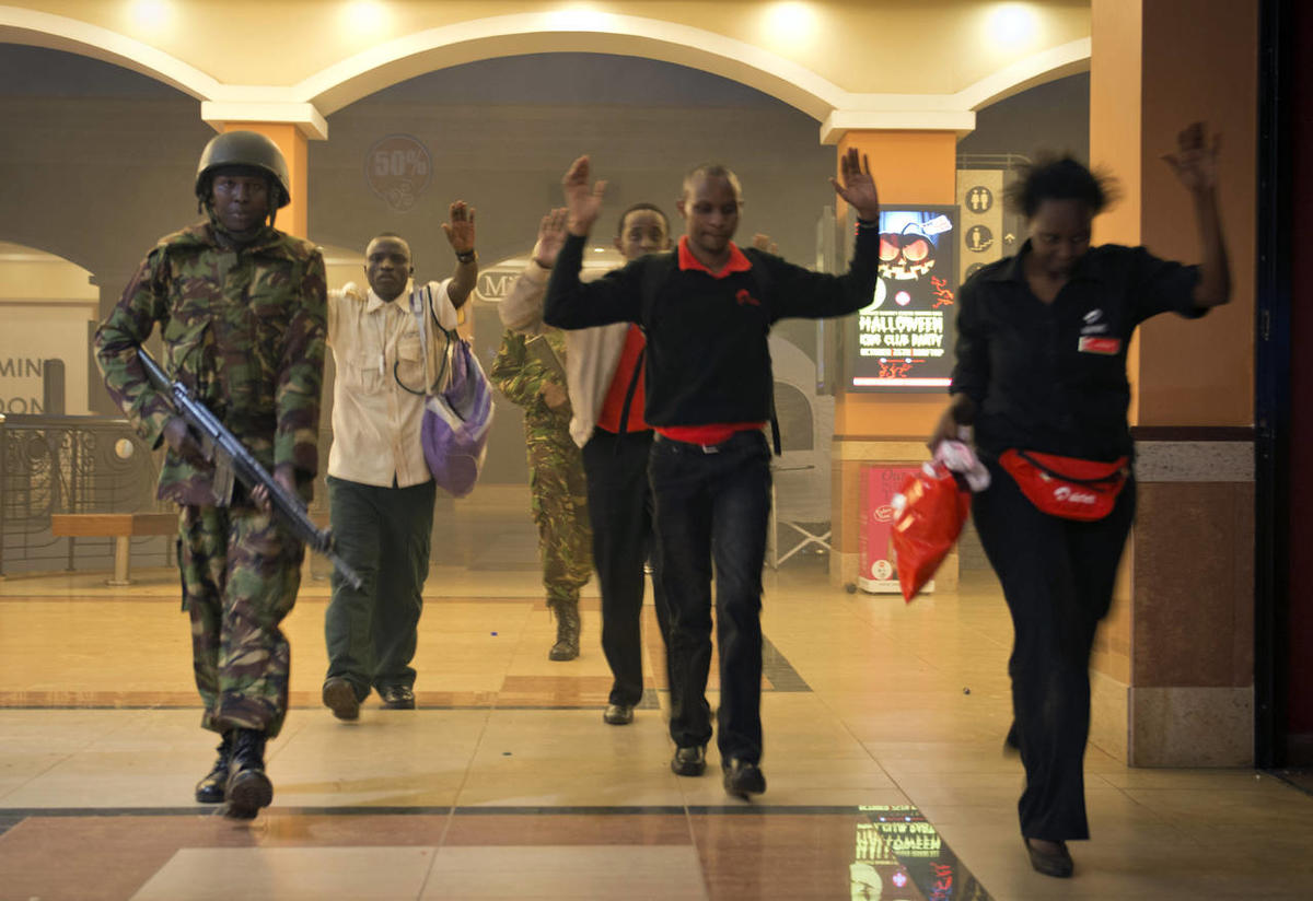 Saturday, Sept. 21, 2013: Nairobi, Kenya_Civilians who had been hiding during a gun battle hold their hands in the air as a precautionary measure before being searched by armed police leading them to safety, inside the Westgate Mall.