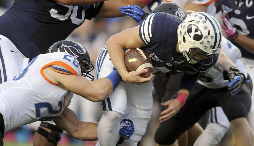 Brigham Young Cougars quarterback Taysom Hill (4) is tackled by Boise State Broncos safety Dillon Lukehart (28) during a game at Lavell Edwards Stadium on Friday, October 25, 2013.