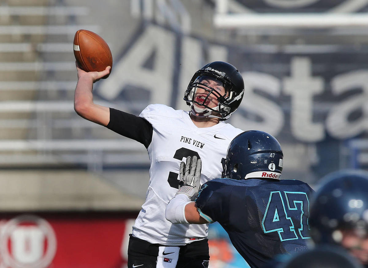 Pine View's Kody Wilstead throws the ball as Juan Diego's Harrison Jones rushes as Pine View High School defeats Juan Diego 48-42 in overtime of the State 3AA High School semi-final football game Thursday, Nov. 14, 2013, in Salt Lake City.