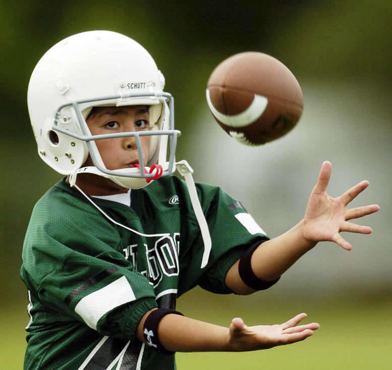 Trae Faumui concentrates on the ball as he takes part in the Dixon Bulldogs little league football practice in Provo. As much of the recent reporting on head injuries in football has focused on legal action taken against the NFL, a couple of authors are t