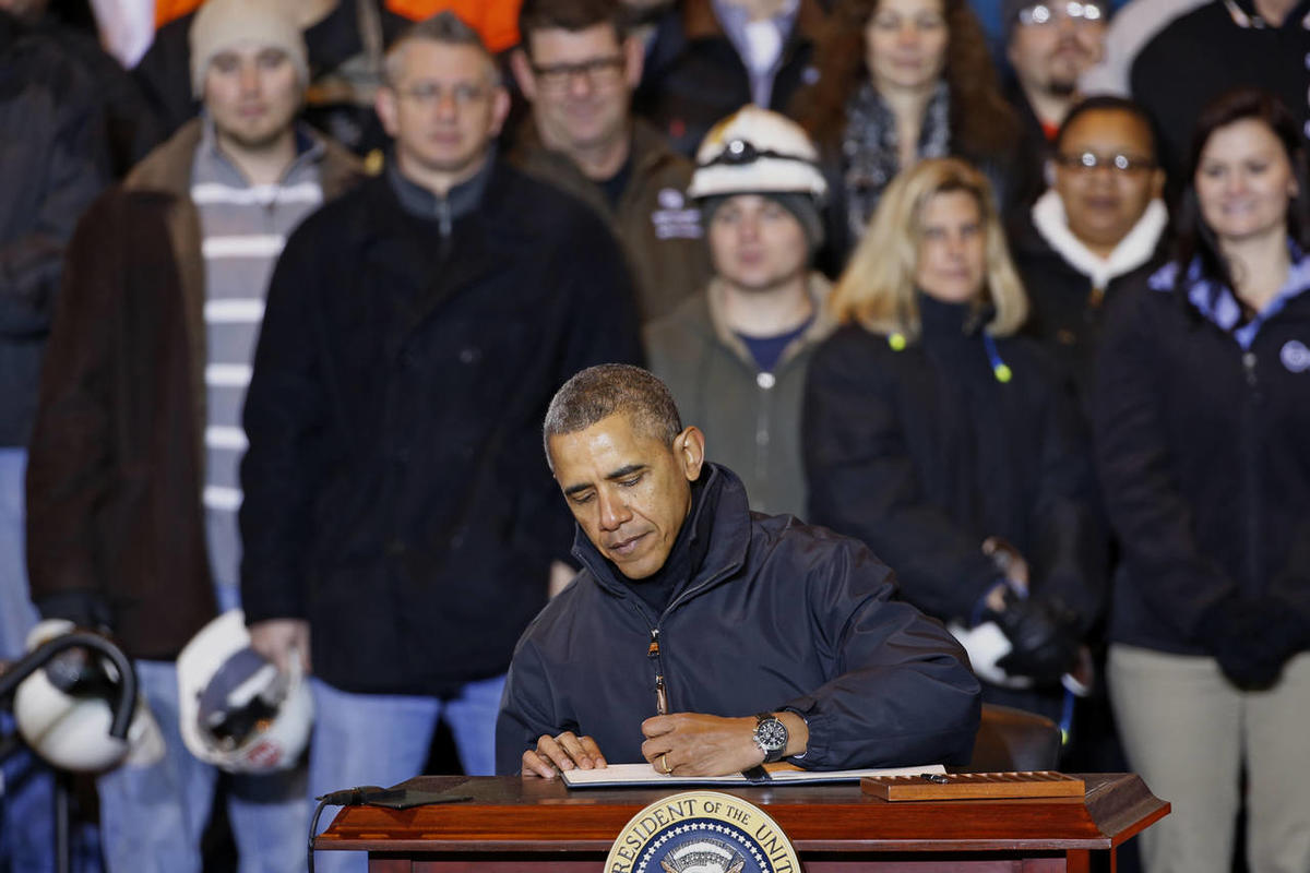President Barack Obama sign an executive order mandating that federal contractors be required to raise the minimum wage they pay their workers to $10.10, Wednesday, Jan. 29, 2014, at the end of an appearance at the US Steel's Mon Valley Works in West Miff