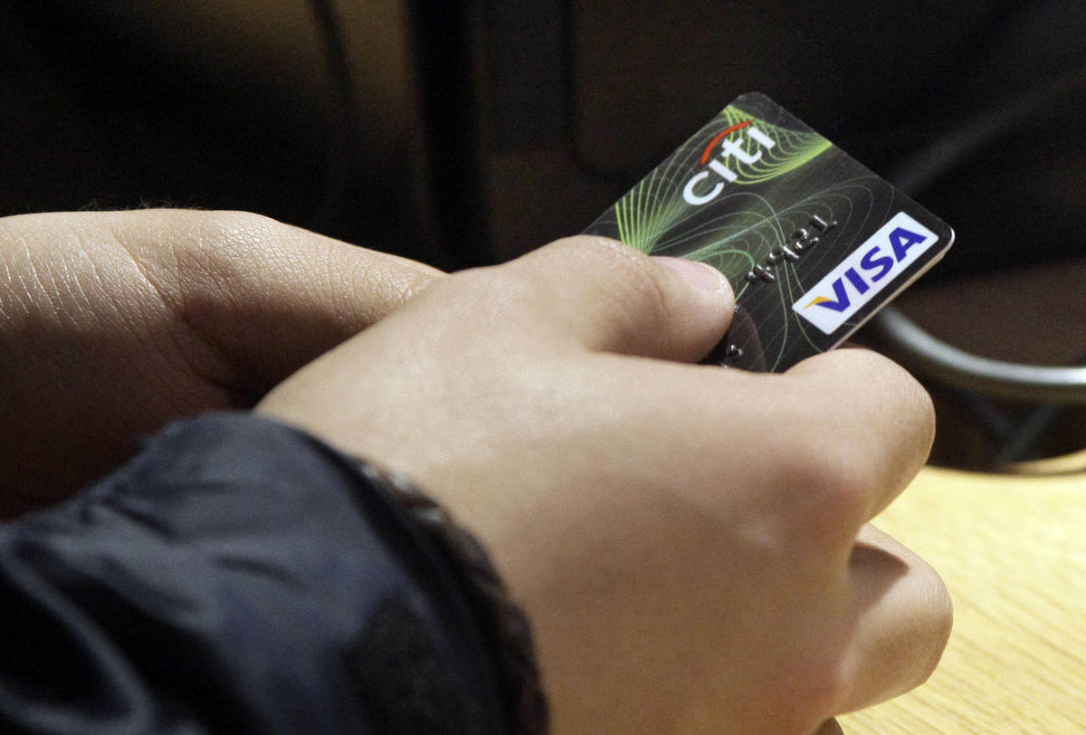 In this May 9, 2012 file photo, a Visa credit card is tendered. Although delinquency rates have trended down for most household debt categories over the past several years, student loan delinquencies are on the rise.