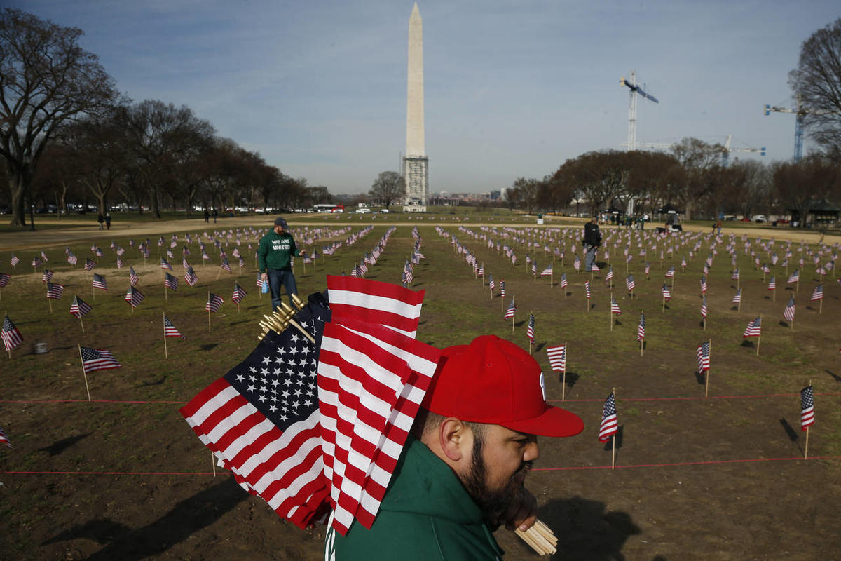 Army veteran Julio Bernal from Takoma Park, Md., works with others from Iraq and Afghanistan Veterans of America (IAVA) to place 1,892 flags representing veteran and service members who have died by suicide to date in 2014 on the National Mall in Washingt