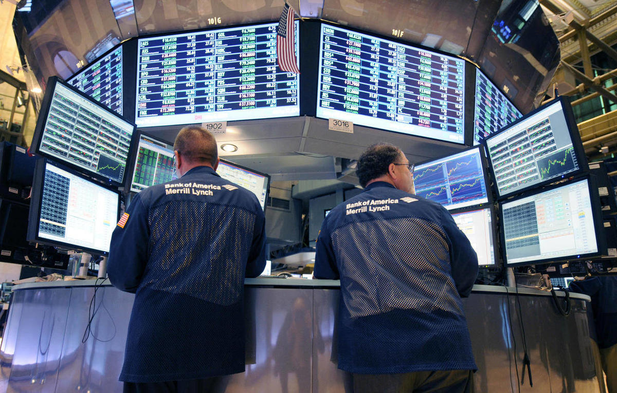 In this Tuesday, Aug. 23, 2011 file photo, Bank of America Merrill Lynch traders work on the floor of the New York Stock Exchange in New York. There are fewer and fewer traders on the NYSE floor because of the dominance of computer trading of securities -