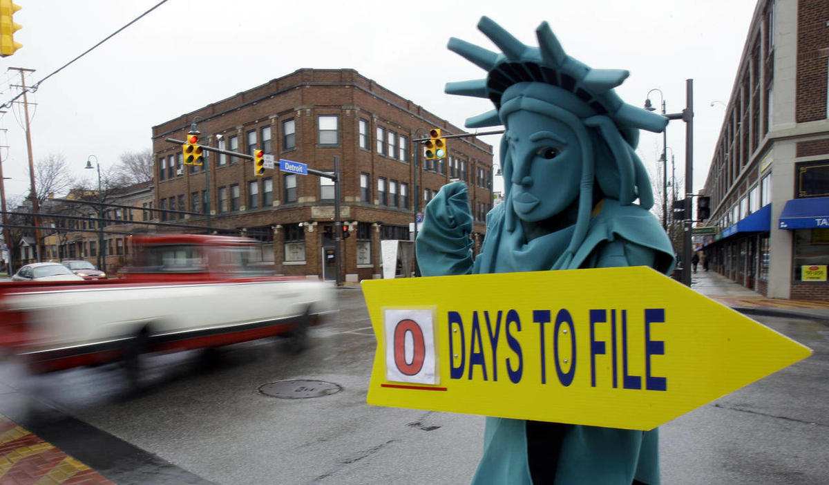 In this Monday, April 18, 2011, file photo, Max Martinez, dressed as the Statue of Liberty, tries to alert motorists on the final day to file taxes.
