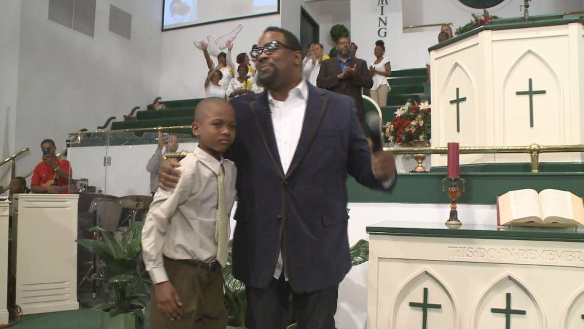 """Willie Myrick is embraced by Grammy Award-winning gospel singer Hezekiah Walker in front of the congregation at Mt. Carmel Baptist Church in Atlanta.  Police say Myrick was abducted from his driveway but was released after singing the gospel song """"Every P"""