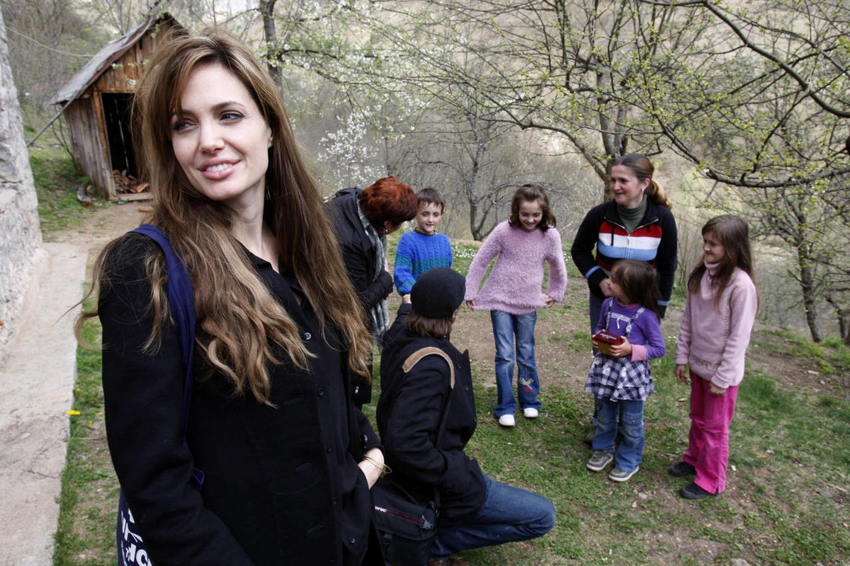 UNHCR goodwill ambassador Angelina Jolie, left, and Brad Pitt, second from left in foreground, visit Bosnian Muslim refugee Sabina Karman, second from left in background, and her four children, in the village of Medjedja, near the eastern Bosnian town of