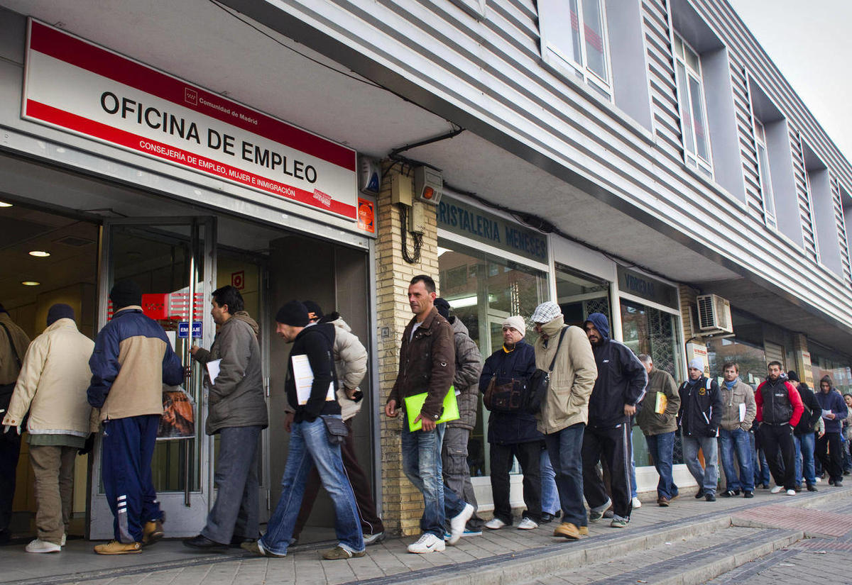 File - In this Dec. 2, 2010 file photo, people queue outside an unemployment registry office in Madrid.