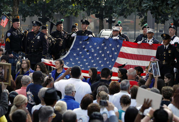 In this Sept. 11, 2013, file photo, the World Trade Center flag is presented as friends and relatives of the victims of the 9/11 terrorist attacks gather at the National September 11 Memorial at the World Trade Center site, for a ceremony marking the 12th