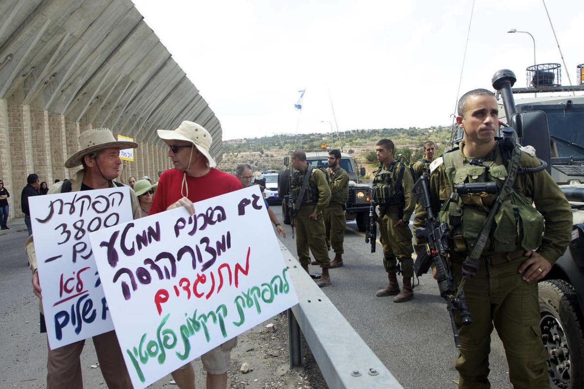 """Israelis protest at a peace rally at the Bethlehem checkpoint, Palestine, to show solidarity with the Palestinians who lost their land when Israel annexed 900 acres of the West Bank in September. Their signs say, """"We are neighbors from MATA and BAR-GIORA"""