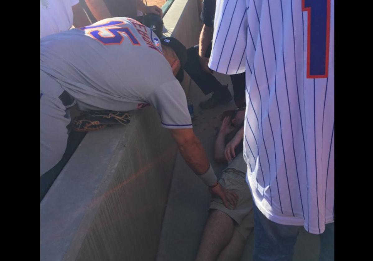 Tim Tebow prays over a fan who collapsed on Tuesday.