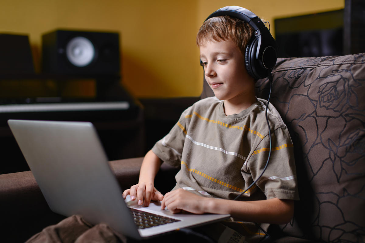 A young boy listens to music and browses the internet.