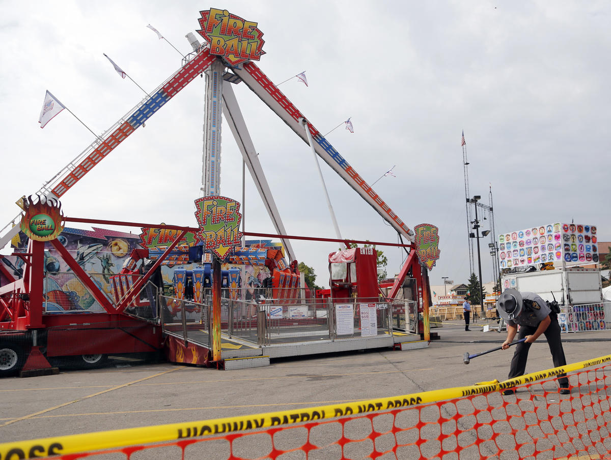 An Ohio State Highway Patrol trooper removes a ground spike from in front of the fire ball ride at the Ohio State Fair Thursday, July 27, 2017, in Columbus, Ohio.  The fair opened Thursday but its amusement rides remained closed one day after Tyler Jarrel