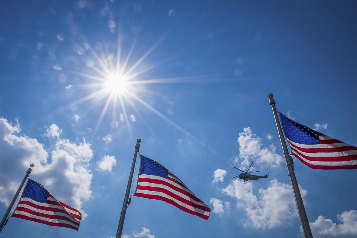Marine One carrying President Donald Trump away from the White House to start his summer vacation, passes the U.S. Flags around the Washington Monument on a hot summer day in Washington, Friday, Aug. 4, 2017. (AP Photo/J. David Ake)
