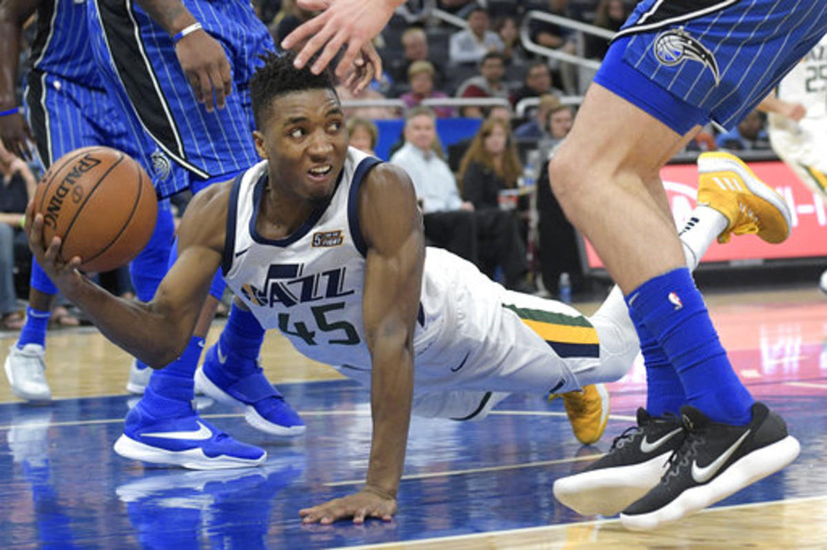 Utah Jazz guard Donovan Mitchell (45) dives after a loose ball to keep it from going out of bounds during the second half of an NBA basketball game against the Orlando Magic, Saturday, Nov. 18, 2017, in Orlando, Fla. The Jazz won 125-85. (AP Photo/Phelan