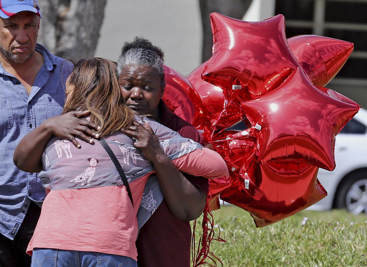 Marjory Stoneman Douglas High School bus driver Pearlie Corker, gets a hug at the school as some teachers return for the first time since the shooting, Friday, Feb. 23, 2018 in Parkland, Fla. Corker arrived at the school as Nicklaus Cruz began to shoot st